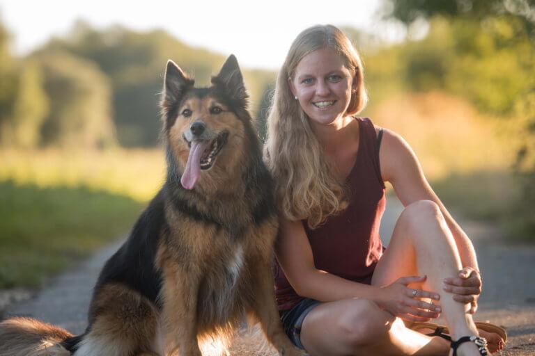 Frau sitzt neben Hund