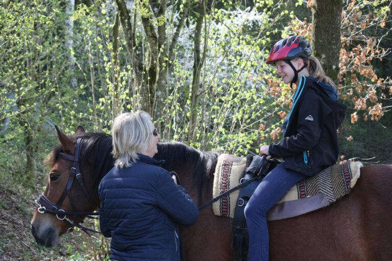 Kind sitzt auf dem Pferd und Reitlehrerin erklärt etwas