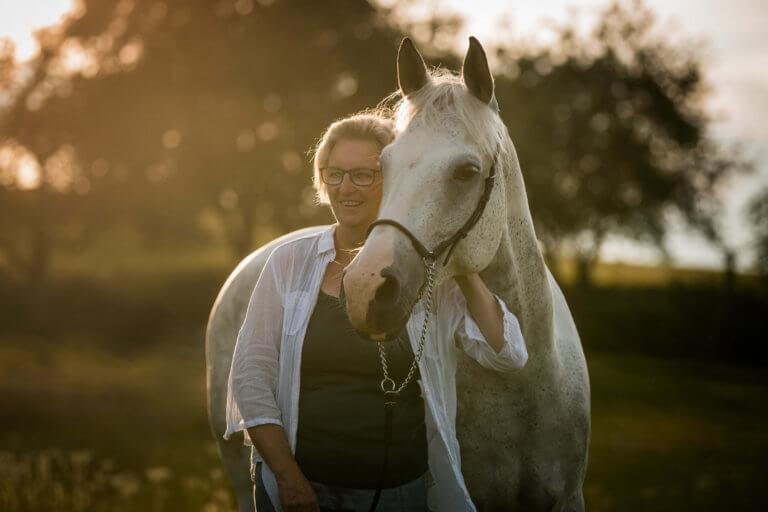 Frau steht neben Pferd